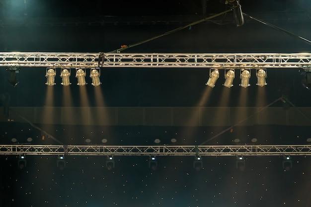 Raggi luminosi dall'illuminazione di un concerto su uno sfondo scuro sullo schermo del proiettore