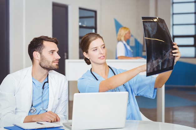 Raggi x d'esame di medico femminile con il collega