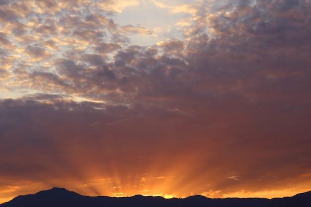 Raggio del sole nascente che splende da dietro la montagna