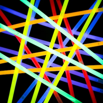 Raggio laser elettrico al neon variopinto realistico su fondo scuro
