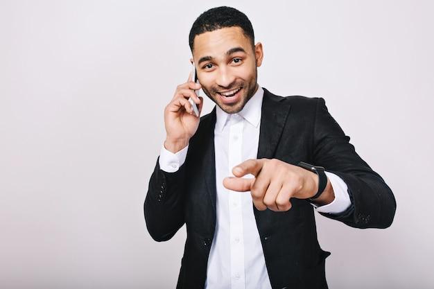 Raggiungendo un grande successo nella carriera di bel giovane in camicia bianca, giacca nera, parlando al telefono. elegante uomo d'affari, sorridente, che esprime felicità, buona fortuna.