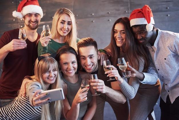 Raggruppa i bei giovani che fanno selfie nella festa di capodanno, le migliori amiche ragazze e ragazzi che si divertono insieme, posando persone di stile di vita emotivo. cappelli di babbo natale e bicchieri di champagne nelle loro mani