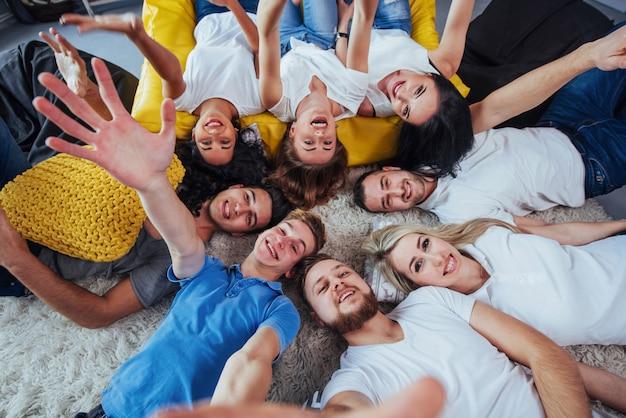 Raggruppa i bei giovani che fanno selfie sdraiato sul pavimento, ragazze e ragazzi dei migliori amici che si divertono insieme, posando stile di vita emotivo