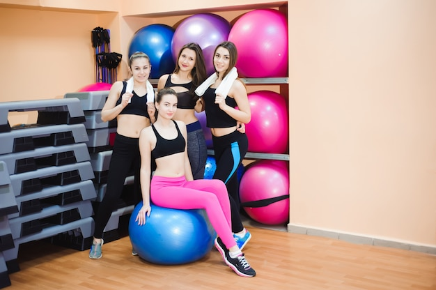 Raggruppa le donne felici allenate in palestra utilizzando l'attrezzatura.