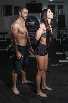 Raggruppi con l'attrezzatura di allenamento con i pesi della testa di legno sulla palestra di sport.