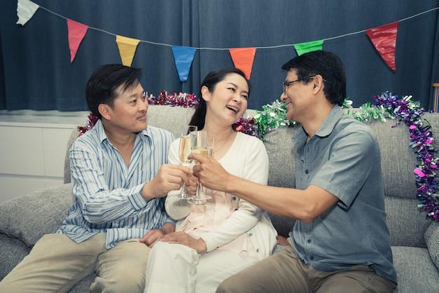 Raggruppi gli amici del partito felice della donna e dell'uomo senior con champagne a casa