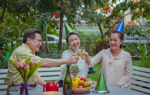 Raggruppi gli amici del partito felice della donna e dell'uomo senior con il giardino del champagne a casa