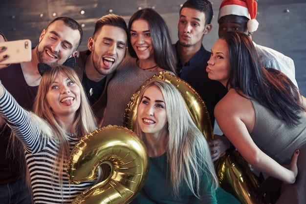 Raggruppi i bei giovani che fanno il selfie nel partito del nuovo anno, le ragazze e i ragazzi dei migliori amici che si divertono insieme, posando il concetto della gente di stile di vita. cappelli di babbo natale e bicchieri di champagne nelle loro mani