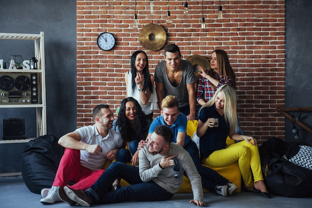 Raggruppi il ritratto dei ragazzi e delle ragazze multietnici con i vestiti alla moda variopinti che tengono l'amico che posa su un muro di mattoni, gente urbana di stile che si diverte, s circa lo stile di vita di insieme della gioventù