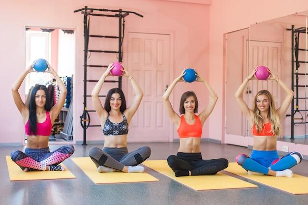 Raggruppi le giovani donne attraenti del og che fanno gli esercizi di coppia con le palle di misura