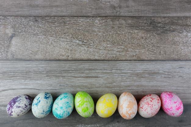 Raggruppi le uova di pasqua variopinte e decorate sul fondo di legno d'annata della tavola. immagine pubblicitaria concetto del festival di pasqua con spazio libero.
