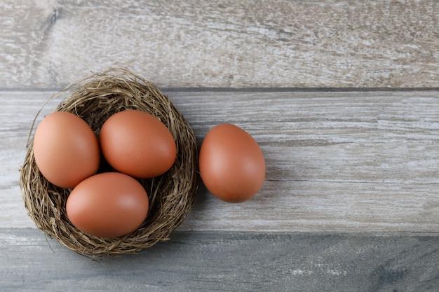 Raggruppi quattro uova di gallina naturali dai prodotti di fattoria nel nido dell'uccello sulla tavola di legno d'annata. immagine pubblicitaria concetto di pasqua o cibo con spazio libero.