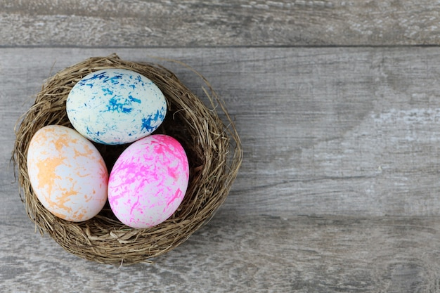 Raggruppi tre uova di pasqua variopinte e decorate nel nido dell'uccello sulla tavola di legno d'annata. immagine pubblicitaria concetto di pasqua o cibo con spazio libero.