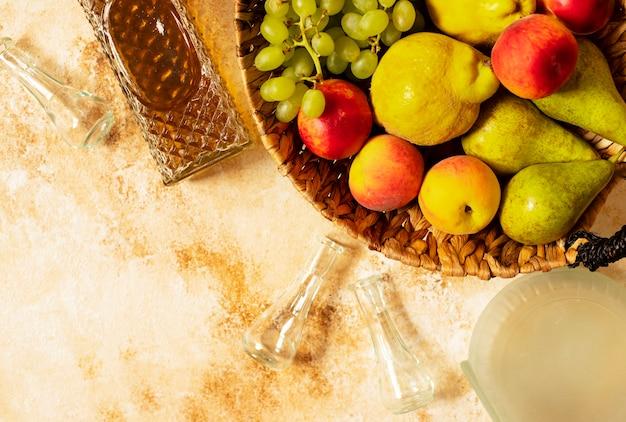 Rakia o rakija il tradizionale brandy alla frutta balcanica. i frutti di cui producono rakia. frutta in un cestino, bottiglie e bicchieri per l'alcol. vista dall'alto. sfondo chiaro vintage. spazio per il testo