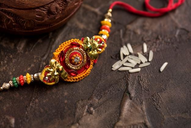 Raksha bandhan con un elegante rakhi e riso sparso. un tradizionale cinturino da polso indiano che è un simbolo di amore tra fratelli e sorelle.