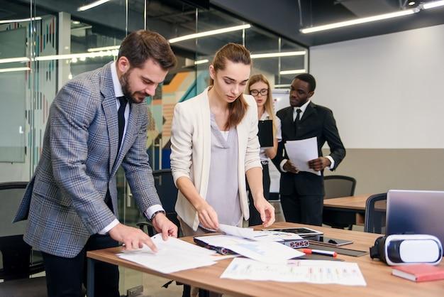 Rallentatore di imprenditore barbuto intraprendente bello in piedi vicino al tavolo della sala del consiglio con il suo collega femmina attento e spiegando i dati dei rapporti