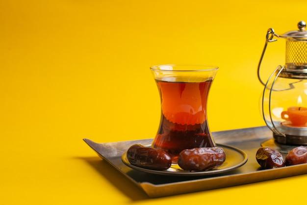 Ramadan kareem festive, primo piano di date sul piatto con lampada candela orientale e tazza di tè nero