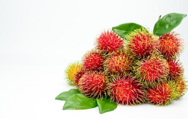 Rambutan maturo rosso fresco (nephelium lappaceum) con le foglie isolate