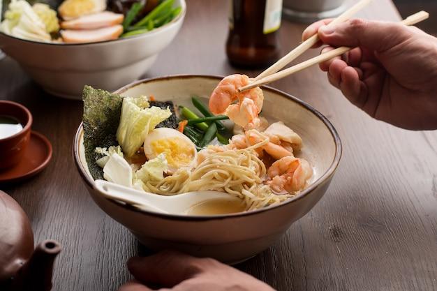 Ramen asiatico mangiatore di uomini con i gamberi e le tagliatelle in un ristorante