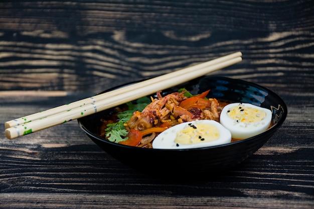 Ramen giapponese con frutti di mare, erbe e uova in salamoia