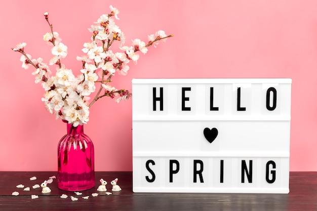Rametti di albero di albicocca con fiori in vaso e lightbox con citazione ciao primavera sul tavolo di legno
