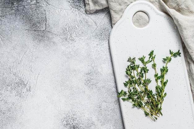Rametti di timo su un tagliere bianco.