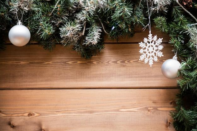 Rami di abete di natale con decorazioni su una tavola di legno.