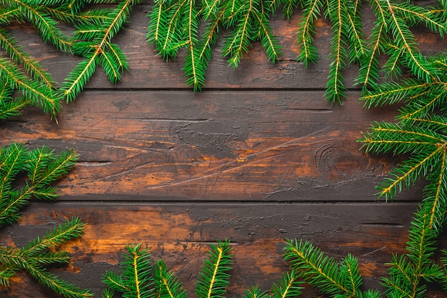 Rami di abete di natale sul bordo di legno rustico marrone con lo spazio della copia