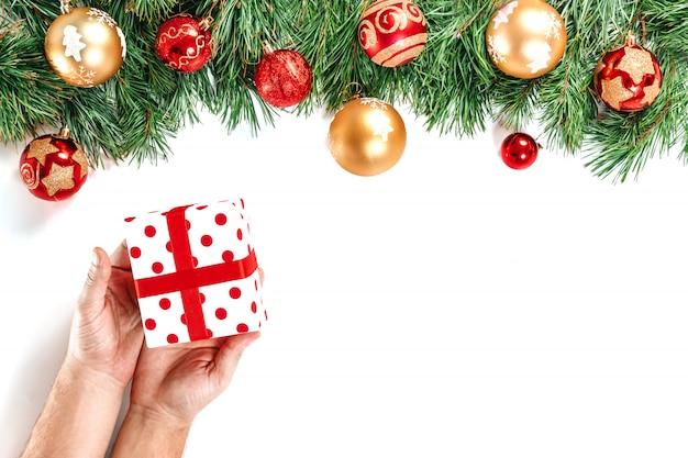 Rami di abete, giocattoli, mani maschii che tengono un regalo, scatola bianca rossa con il nastro, isolata su bianco. isolato. buon natale e un felice anno nuovo.