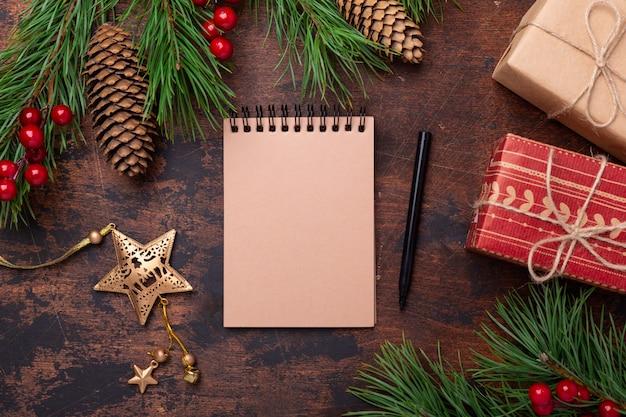 Rami di abete, regali e un quaderno su uno sfondo di legno. nuovi obiettivi. sfondo di natale. vista dall'alto, copyspace.