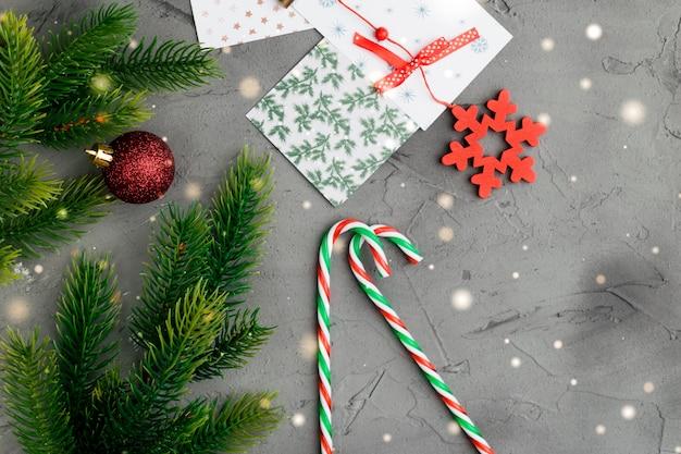 Rami di abete su sfondo grigio cemento con scatola regalo rosso. spazio per il testo distesi.