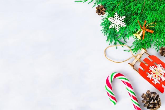 Rami di alberi di natale, coni e un giocattolo di slitta rossa con un fiocco di neve e un bastoncino di zucchero su uno sfondo chiaro, situato a destra. concetto di capodanno per biglietti di auguri, inviti con spazio di copia.