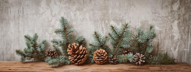 Rami di albero di natale con coni su una tavola di legno contro un muro di cemento grigio.