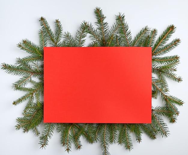 Rami di albero di natale con un foglio rosso vuoto