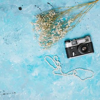 Rami di fiori con macchina fotografica e perline sul tavolo