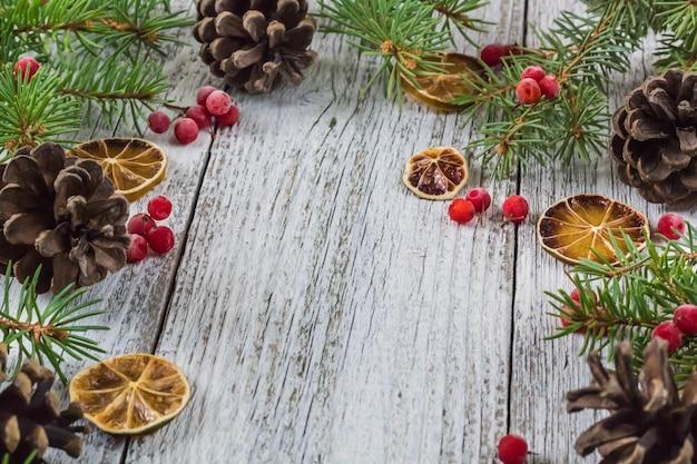 Rami di natale con coni bacche di viburno e limone secco