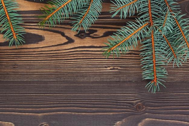 Rami di pino di natale sul fondo del bordo di legno con copyspace