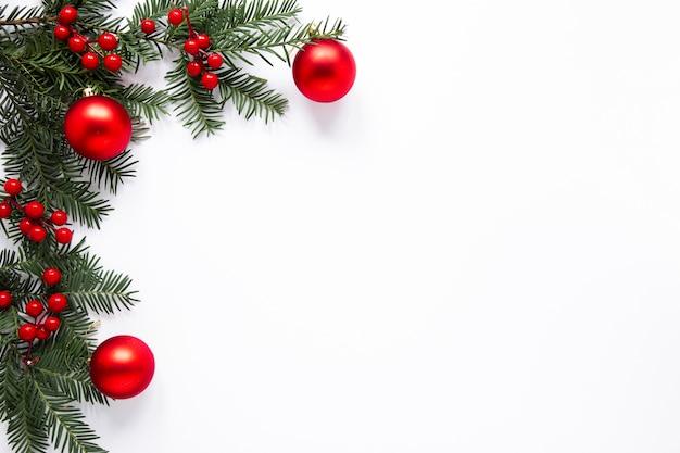Rami di pino e decorazioni rosse con spazio di copia