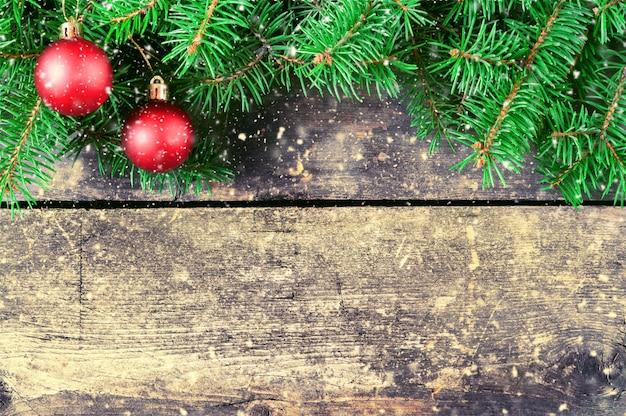 Rami di un albero di natale su vecchie schede. sfondo di natale. decorazioni natalizie. anno nuovo sfondo xmax background. immagine tonica. neve che cade.