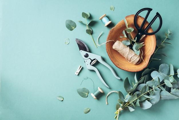 Rami e foglie di eucalipto, potatore da giardino, forbici, piatto di legno