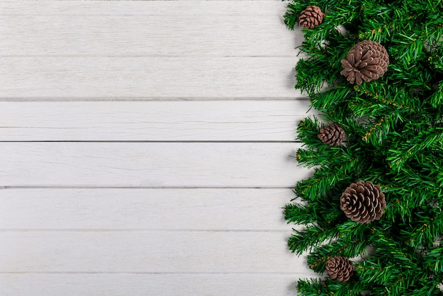 Rami e pigne dell'abete sul fondo bianco del bordo di legno