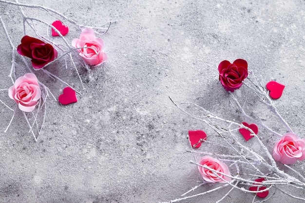 Rami nella neve con boccioli di rosa e rosa rossa e cuori su uno sfondo concreto