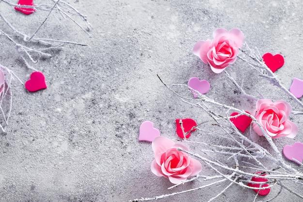 Rami nella neve con boccioli di rosa rosa e cuori su uno sfondo concreto
