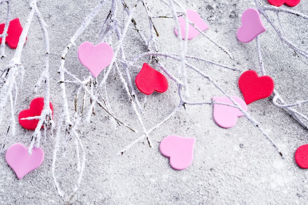 Rami nella neve con cuori rosa e rossi su uno sfondo concreto