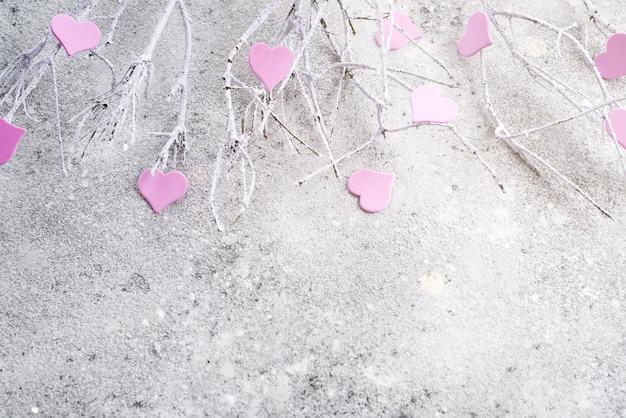 Rami nella neve con cuori rosa su uno sfondo concreto