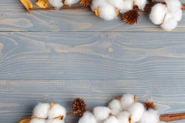Ramo con fiori di cotone su legno