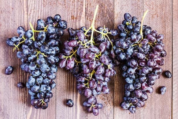 Ramo d'uva nera su legno scuro