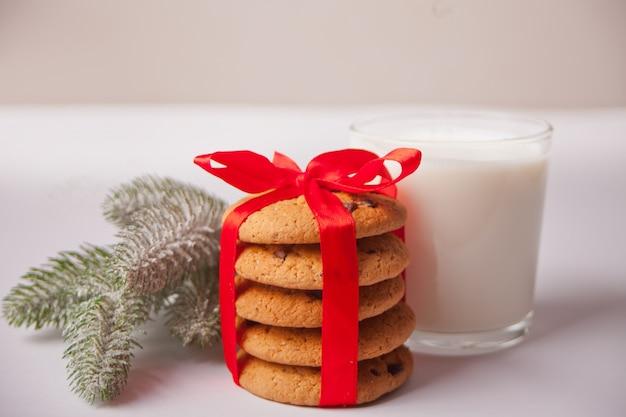Ramo del bicchiere di latte, dei biscotti e dell'albero di natale