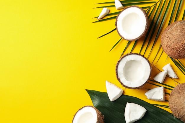 Ramo della palma e della noce di cocco su giallo. frutta tropicale
