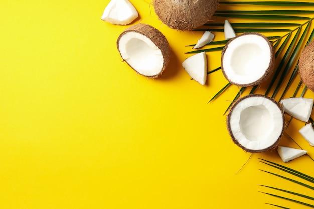 Ramo della palma e della noce di cocco sulla tavola gialla. frutta tropicale